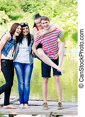 group of young people teenage friends happy smiling & looking at camera having fun outdoors
