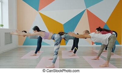 Group of young people training in yoga studio concentrated on bending asana