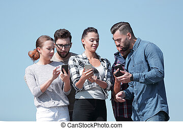 group of young people using smartphones.