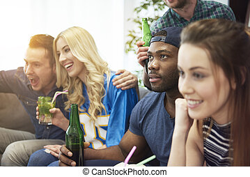 Group of young people watching soccer match