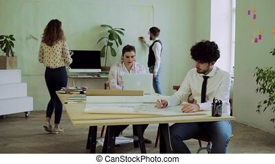 Group of young people working together in an office....