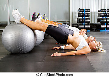 group of young people workout in gym with fitness balls