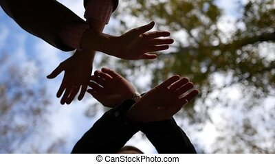 group of young place their hands together in the center of a circle