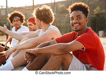 Group of young positive multiethnic men basketball players ...