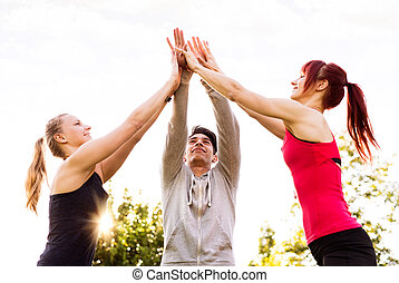 Group of young runners in park doing high five gesture.