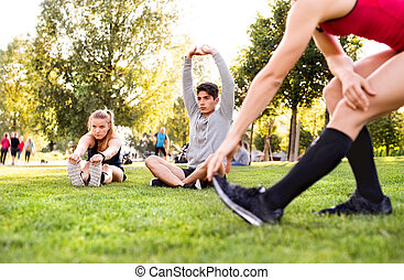 Group of young runners stretching and warming up in park.