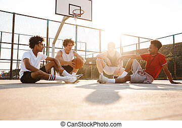 Group of young smiling multiethnic men basketball players ...