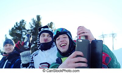 Group of young snowboarders on the slopes in sunny winter day taking selfie drinking beer and have great time