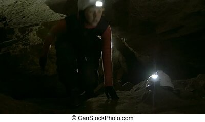 Group of young speleologists climb up in the dark narrow...