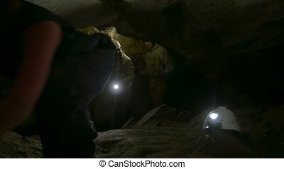 Group of young speleologists explores the dark narrow cave,...