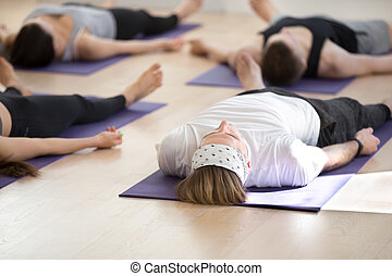 group of young sporty people in adho mukha svanasana pose