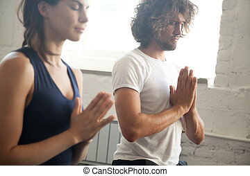 Group of young sporty people making namaste gesture, man and...