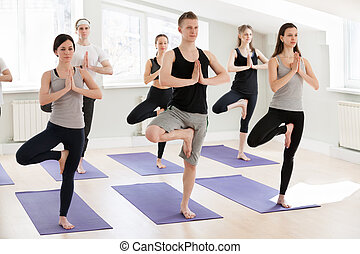 group of sporty people practicing yoga doing warrior one