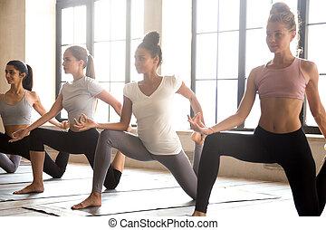 Group of young sporty women practicing yoga, doing anjaneyasana