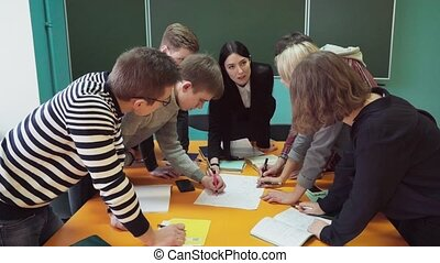 Group of young students making task under teacher's...