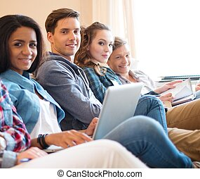 Group of young students preparing for exams in apartment...