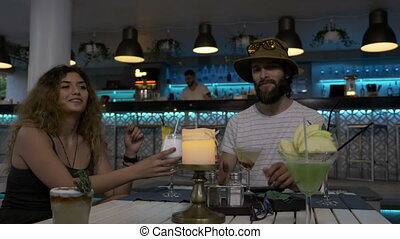 Group of young stylish friends sitting at table in the club lounge enjoying alcohol cocktails toasting and having fun in weekend
