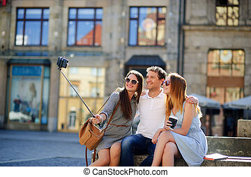Group of young tourists makes selfie on the background of an old building