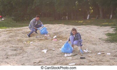 Group of young volunteers picking up garbage on the beach.