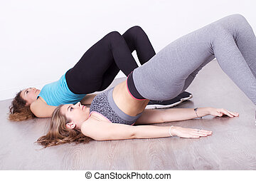 group of young women doing exercise abdominal crunches in the gym centre sport