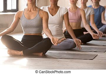Group of young women doing Sukhasana pose