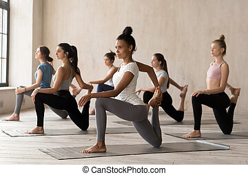 Group of young women practicing yoga, doing Horse rider exercise