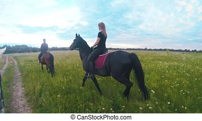 Group of young women rides on horseback in the field