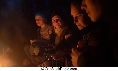 Group og friends singing songs to the guitar in front of campfire in the night forest