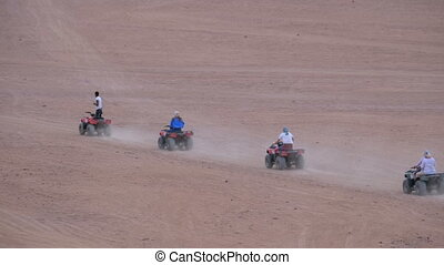 Group on Quad Bike Rides through the Desert in Egypt Driving...
