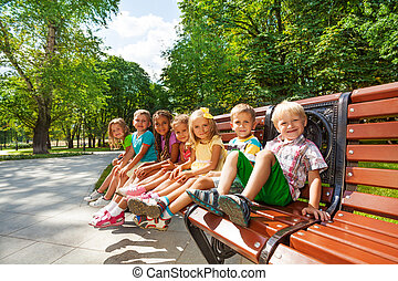 Group or kids rest on bench in park