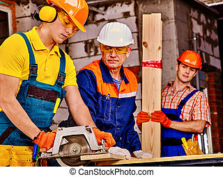 Group people builder with circular saw . - Happy group...