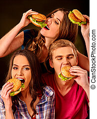 Group people eats with relish hamburgers .