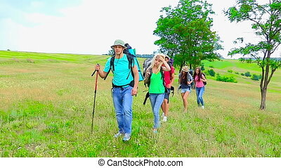 Group people with backpacks and dog hiking outdoor. Used steadicam.