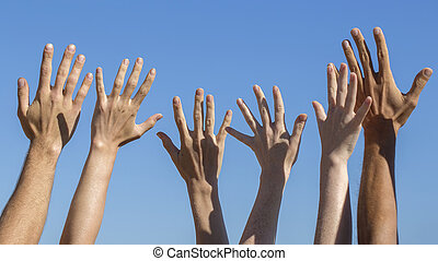 Group raising hands against blue sky background