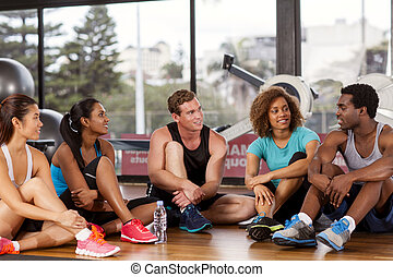Group relaxing before a gym class - Multi-ethnic group...