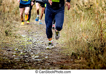 group runners running uphill in autumn trail of mud and...