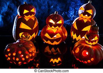 Group strange halloween pumpkins on black background with...