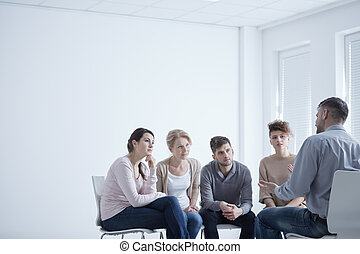 Group therapy for social anxiety - People sitting in circle...