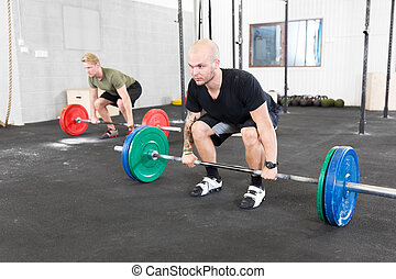 Group trains deadlift at fitness gym center - Two men taking...