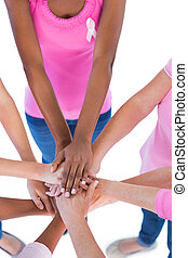 Group wearing pink and ribbons for breast cancer putting hands together on white background