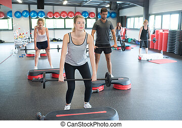 group with weight lifting bar in crossfit exercise