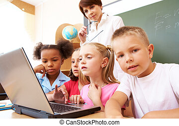 Group work - Photo of serious classmates and teacher looking...