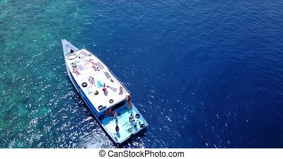 group young beautiful girls sunbathing on a boat with aerial view in clear aqua blue sea water and blue sky