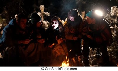 Group young people sitting in winter forest by the fire. A young woman telling her friends a scary story, holding a flashlight near her face