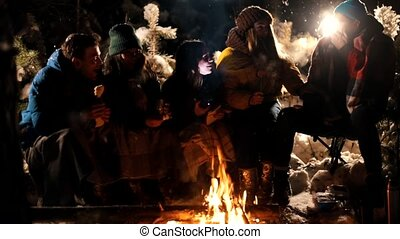 Group young people sitting in winter forest by the fire. A young woman telling her friends a scary story, holding a flashlight near her face. A young man got scared