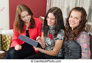 Group young women friends chatting at home and using laptop to look at new photo or browsing internet