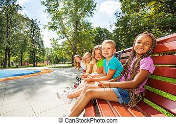 groupe enfants, banc, dans parc