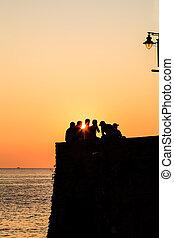 groupe, gens, riomaggiore, coucher soleil, italie, regarder