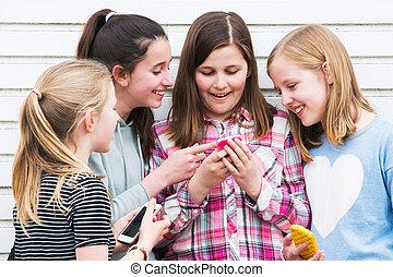 groupe, mobile, filles, jeune regarder, téléphone, dehors, message