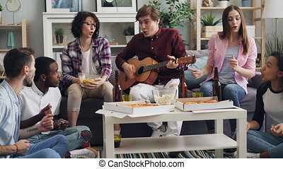 groupe, multiethnic, délassant, chant, guitare, maison, fête, amis, jouer